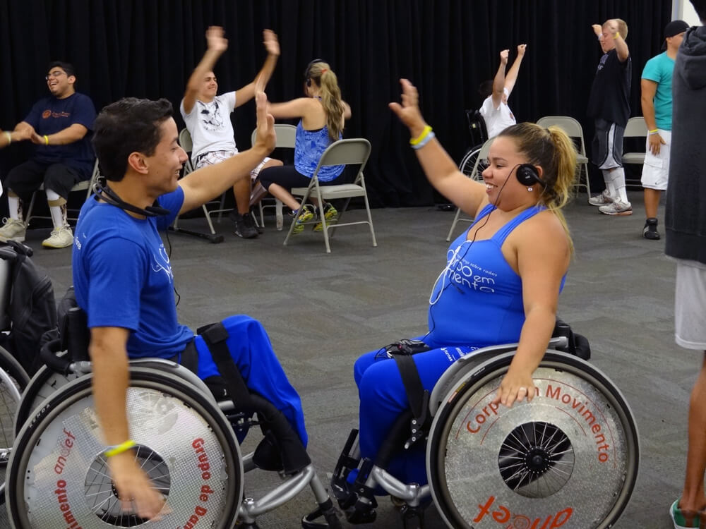 Two people in wheelchairs, facing each other and dancing.