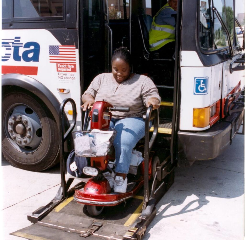 A woman using an electric scooter rides a lift to get onto a bus.