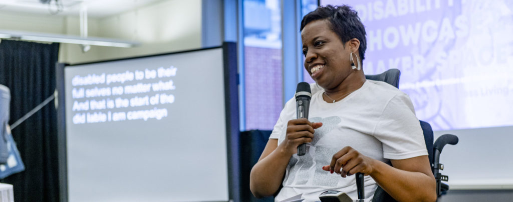 Image is a Black woman holding a microphone as she gives a presentation. She uses a power chair.