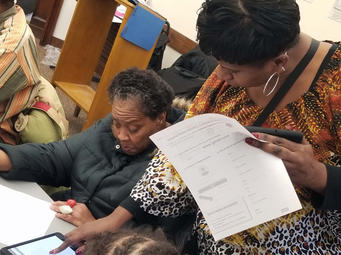 An instructor assists an adult financial literacy student with a budgeting exercise.