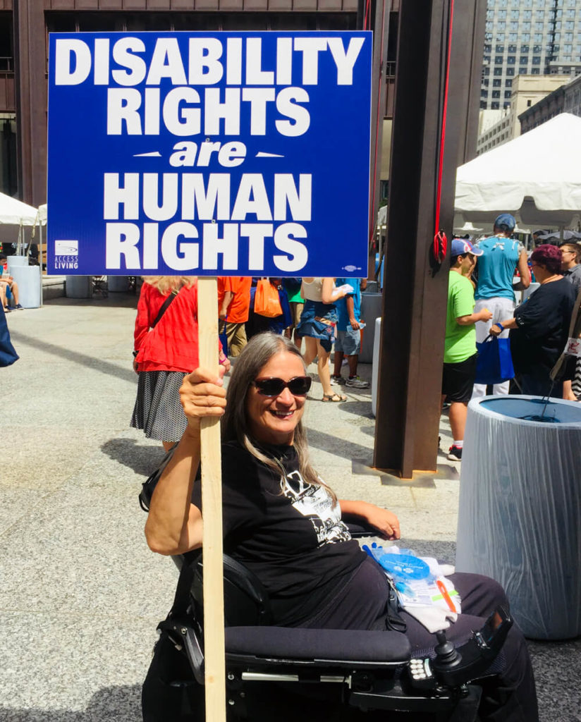 Woman in a wheelchair holds a sign that reads disability rights are human rights.