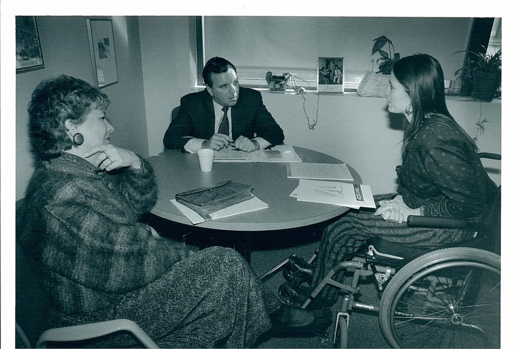 A black and white photo of disability rights activist Marca Bristo in a meeting with Mayor Richard Daley and Maggie Daley.