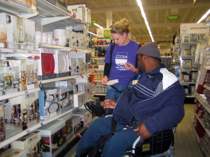 Image is of two people shopping in a grocery store. One man is standing, the other uses a wheelchair.