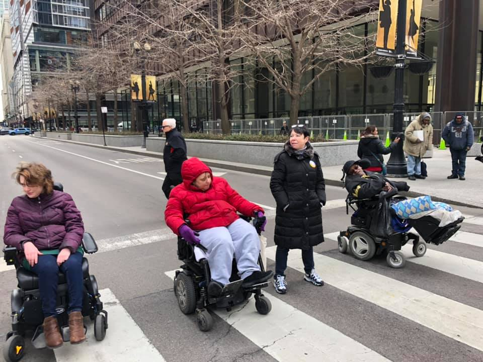 Three people in wheelchairs and one woman who is standing block the street.