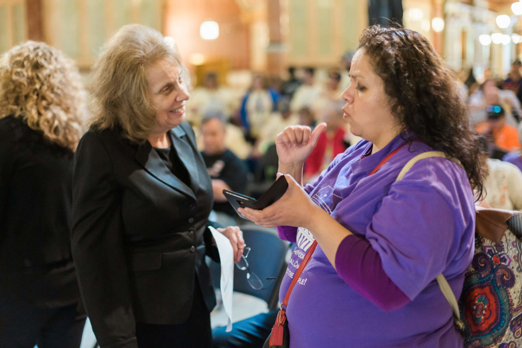 A disability advocate speaks with a legislator.