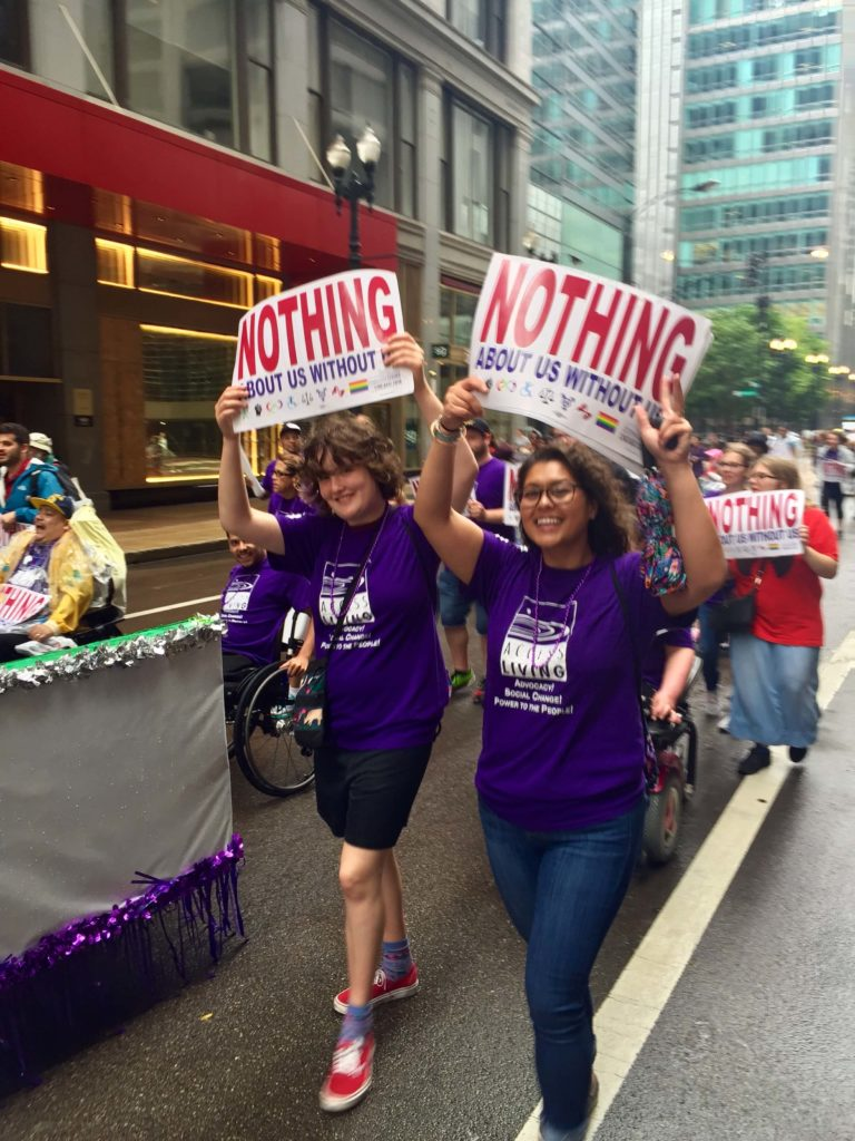 Disability advocacy: smiling woman and girl carrying signs in a parade.