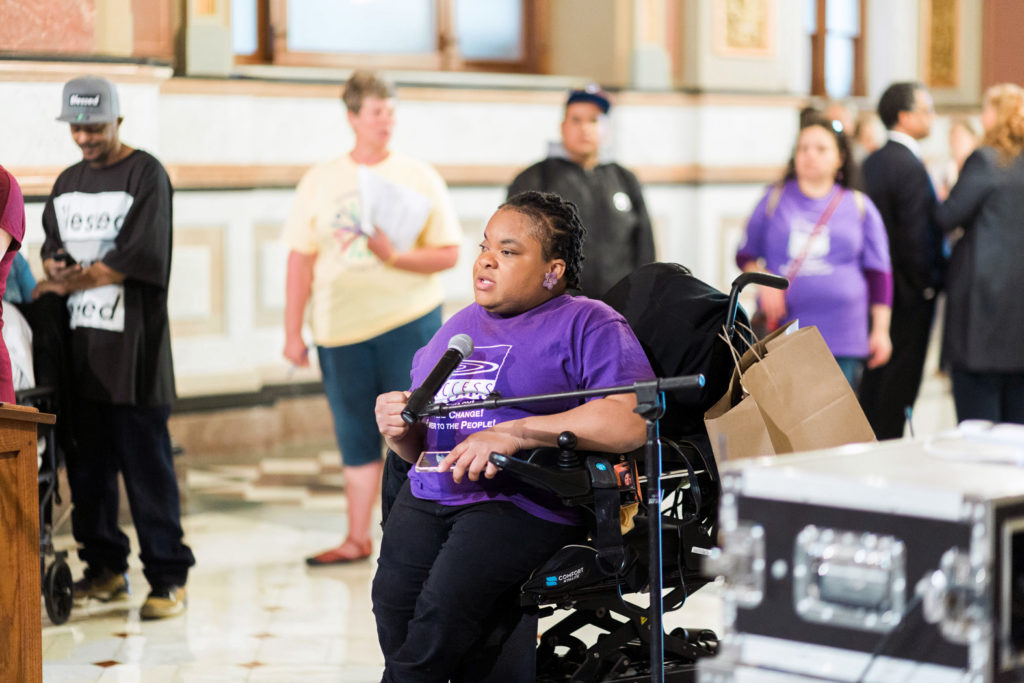 Dr. Angel Miles, a black woman using a power chair, speaks at a rally in Springfield, Ill.