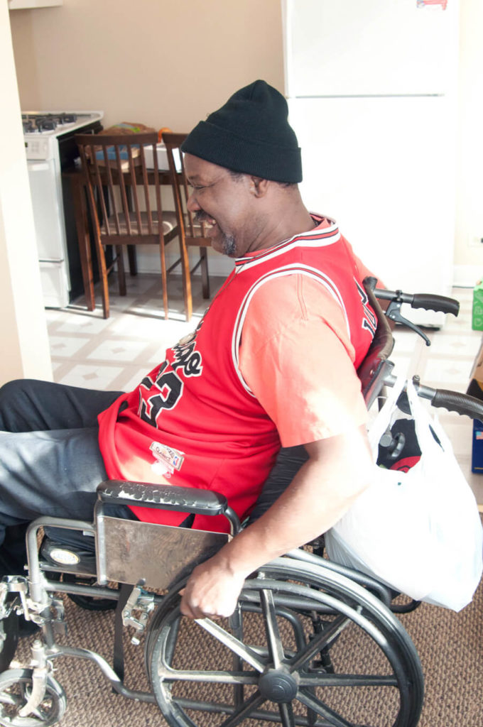 A Black man, a wheelchair user, smiles as he moves into his own home.