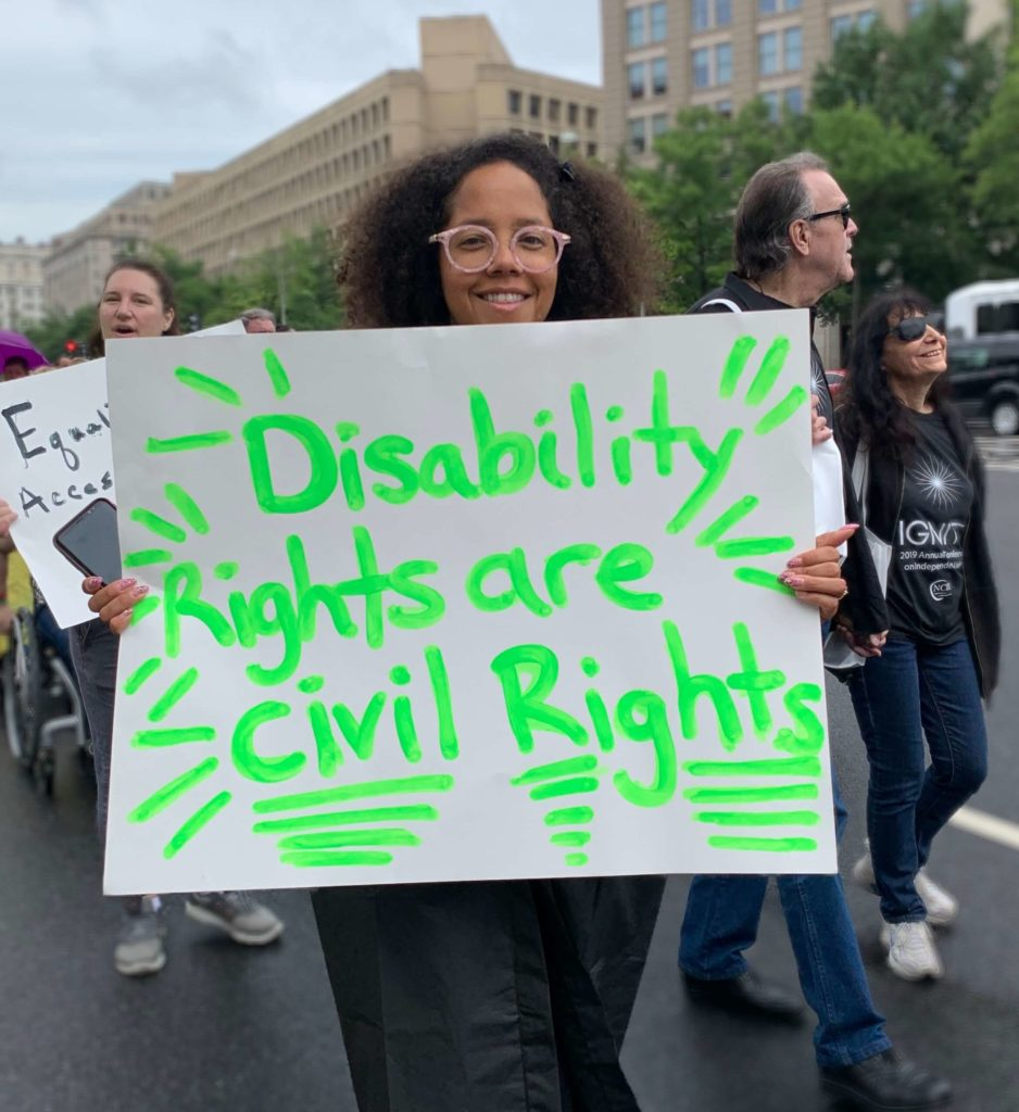 A young Black woman carrying a sign that reads, 'Disability rights are civil rights'.