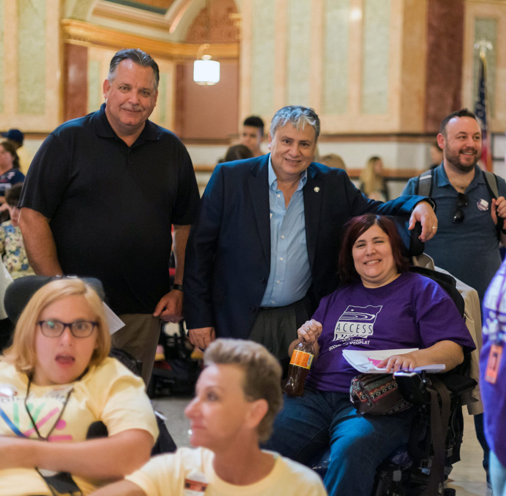 Immigration advocates, two are men who are standing and a woman using a wheelchair attending a rally.