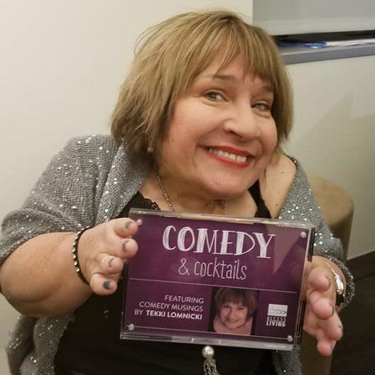 Comedian Tekki Lomnicki holding one of her comedy albums.