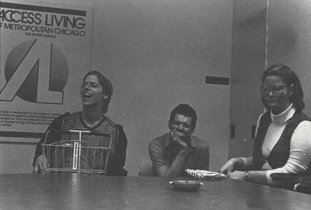 A black and white photo of Access Living consumers and staff at a workshop in 1980.