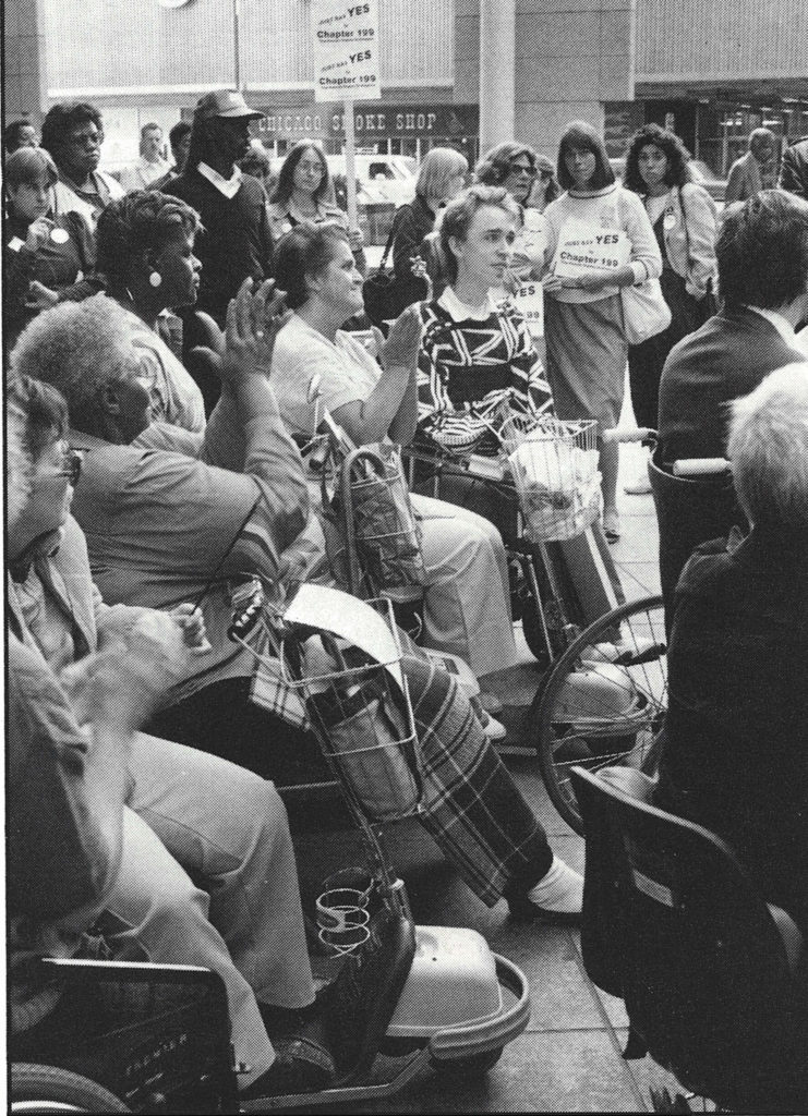 A black and white photo of a crowd of disability activists rallying together.