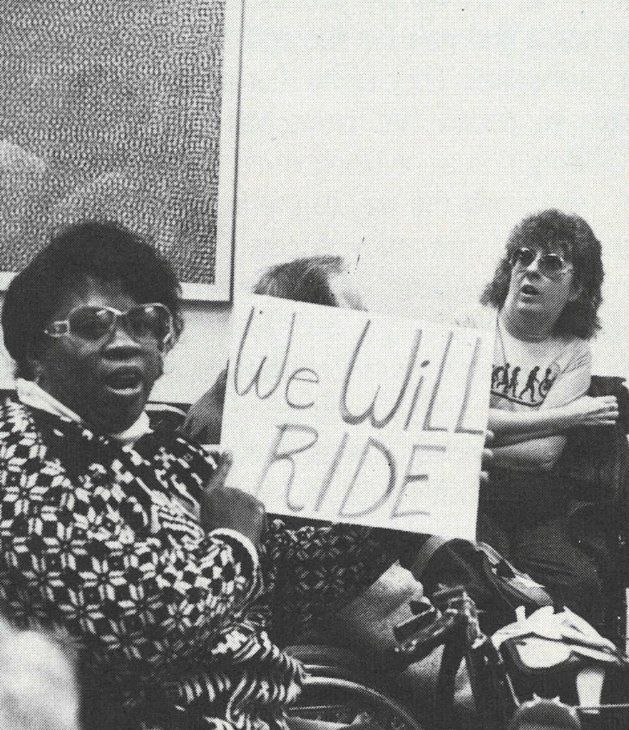 "A Black woman holding a protest sign that says, ""We Will Ride."""
