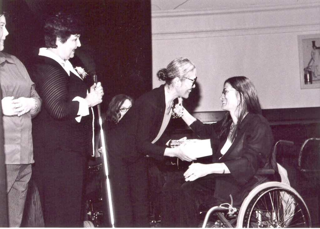 Yoshiko Dart, a petite Asian woman, congratulates Marca Bristo, a white woman using a manual wheelchair.