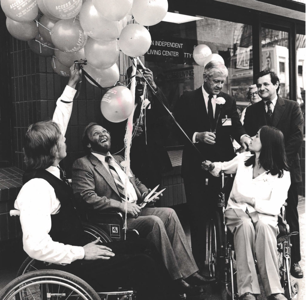 Three wheelchair users, including Marca Bristo, cut celebratory balloons in front of Access Living's original location.