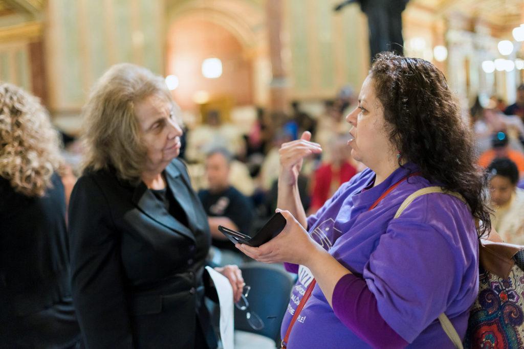 An Access Living advocate speaking with a legislator in Springfield, IL.
