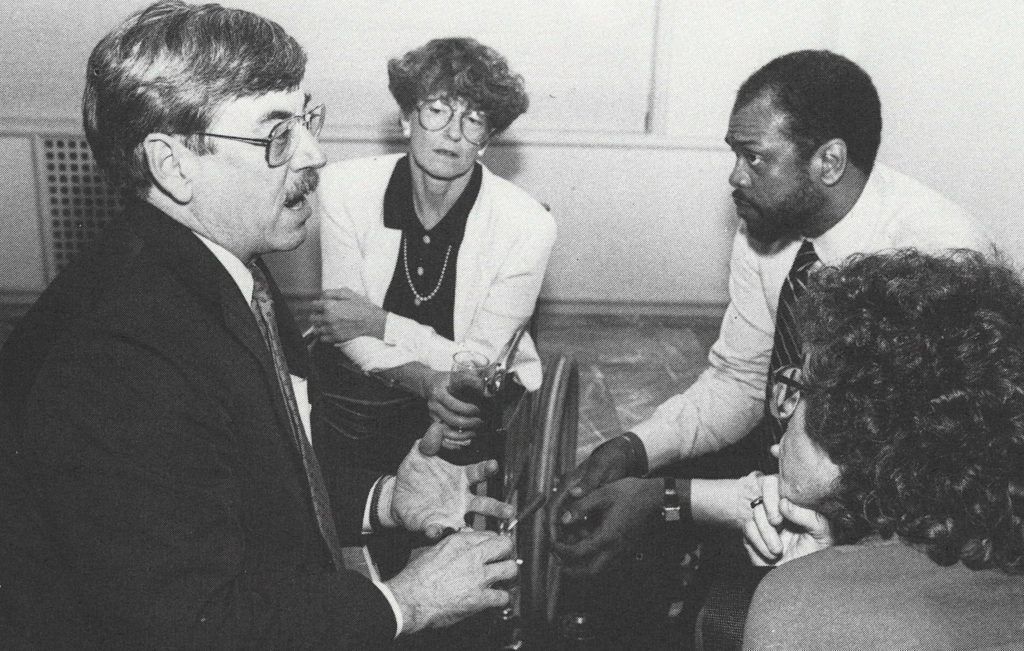 A black and white photo of four professionally dressed people in conversation.