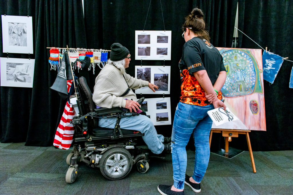 Attendees of an art showcase examine displayed artwork.