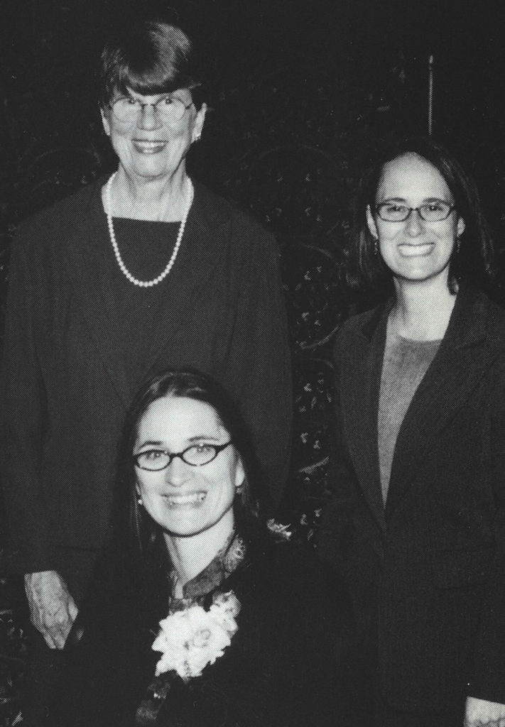 A black and white photo of three women posing together at a formal event.