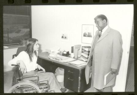 Marca Bristo in her wheelchair at her desk talking to Mayor Harold Washington.