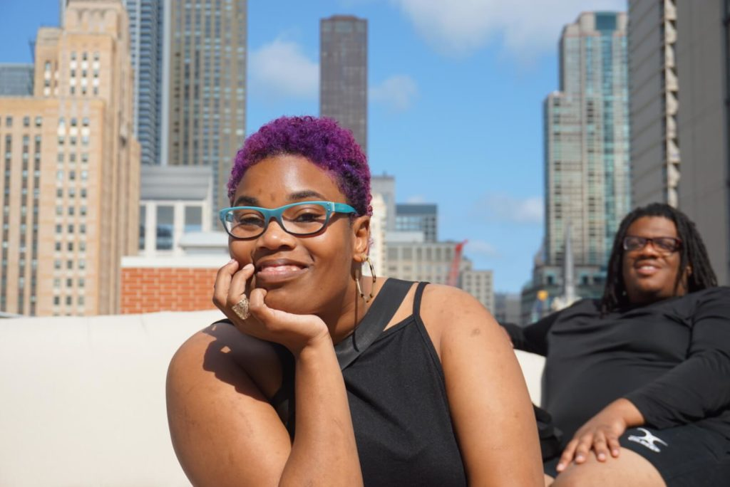 A young black woman with purple hair smiles at the camera.