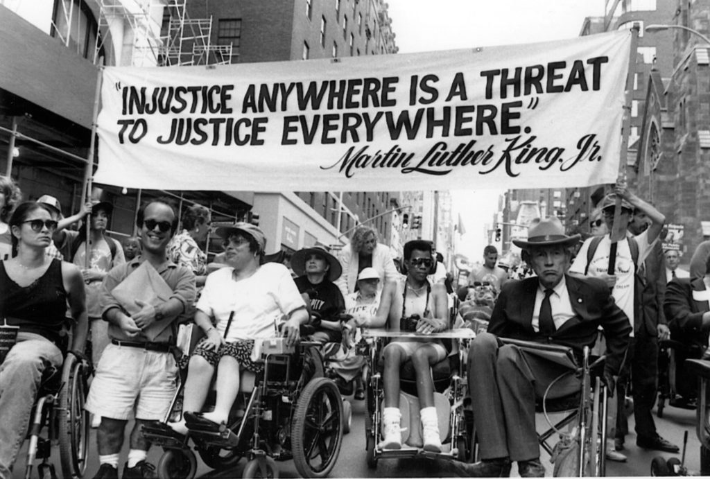 Black and white photo of a disability march in support of the ADA in 1990.