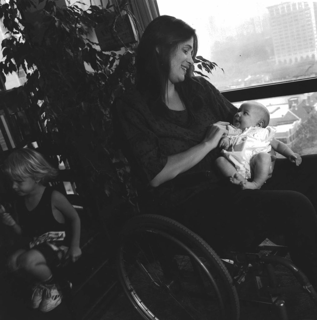 Black and white photo of Marca Bristo sitting in her wheelchair and holding her baby daughter.
