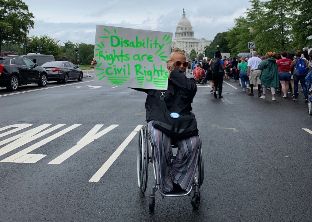 "A woman using a manual wheelchair holding a sign that reads ""Disability rights are civil rights."""