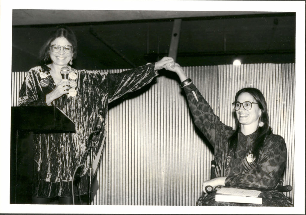Black and white photo of Gloria Steinem and Marca Bristo, raising clasped hands overhead.