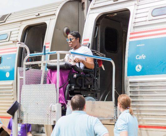 A wheelchair user using a wheelchair lift to disembark from a train.