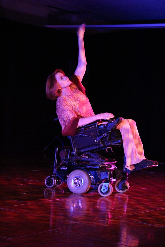 A woman performing an integrated dance. She uses a power wheelchair.