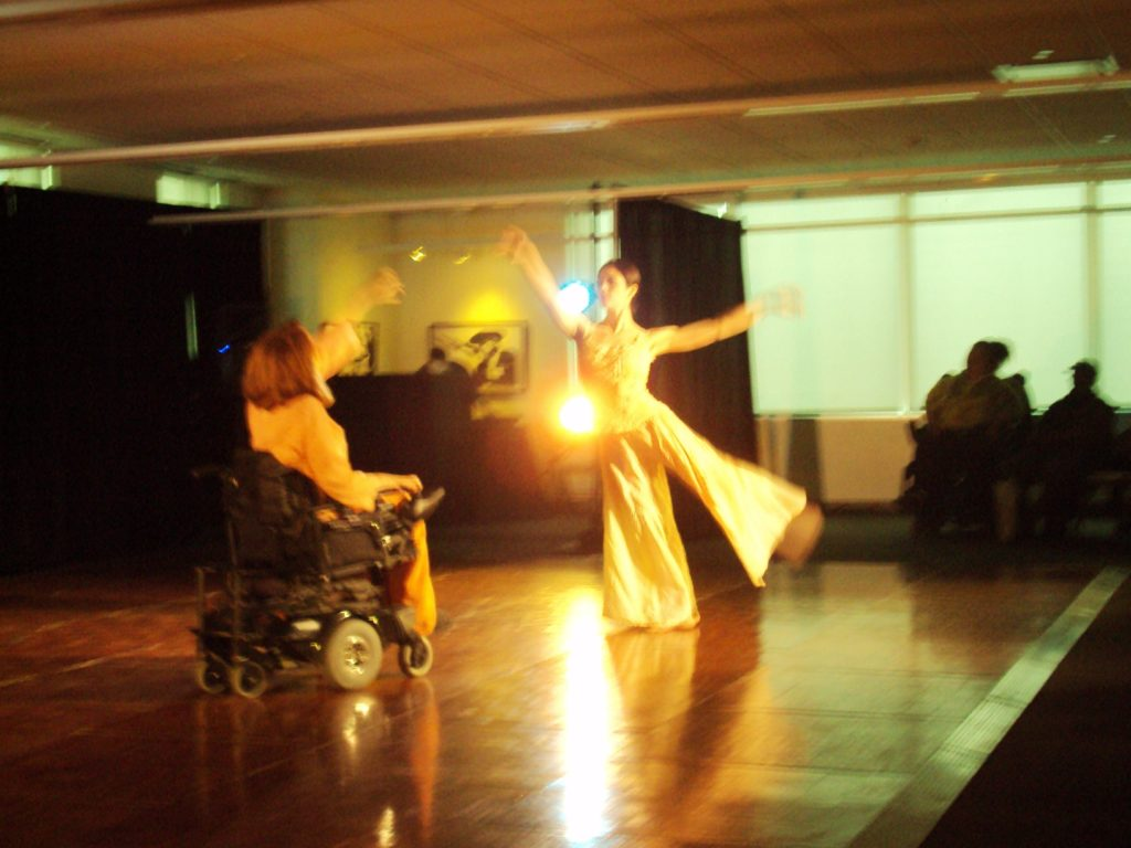 A woman in a wheelchair dances with an abled woman in a integrated dance performance.