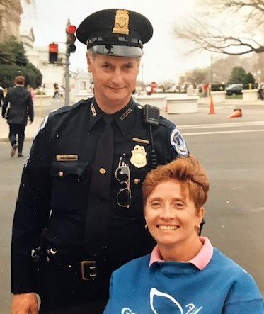Image is of Ginger Lane, a wheelchair user, with a police officer in Washington D.C.