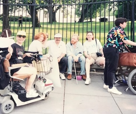Image is of six disability advocates sitting on a bench in front of the White House in demonstration for the ADA.