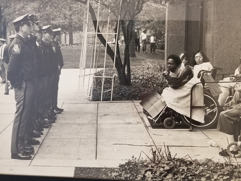 Image is a black and white photograph. Disability activists use their bodies and wheelchairs to block the entrance to a building. Many of them have protest signs. A row of police officers stand at attention in front of the protesters.