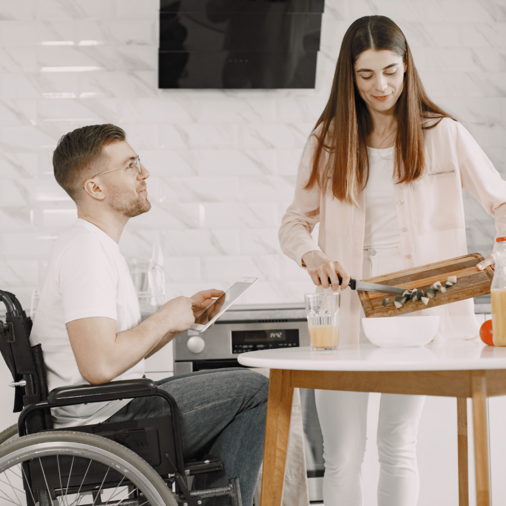 Seated by a kitchen table, a man in a wheelchair points to the screen of an iPad. He is smiling at a woman with long hair as she transfer chopped vegetables from a cutting board to a bowl.